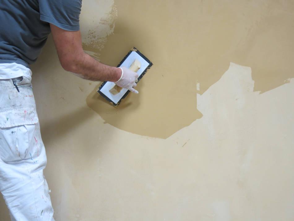 Profesional aplicando microcemento en pared con llana de goma