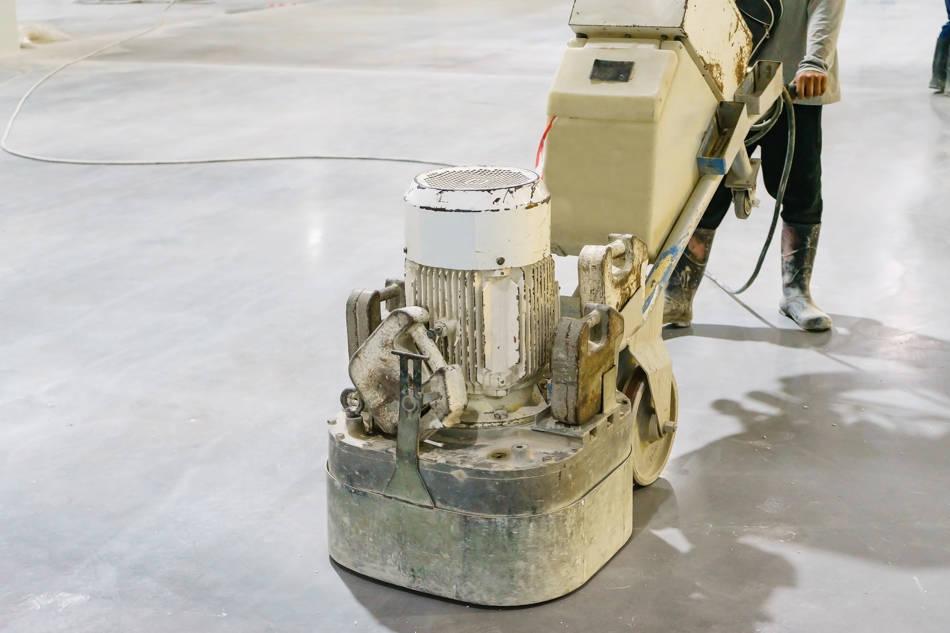 operario puliendo pavimento cemento pulido con pulidora rotativa.
