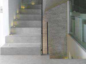 Graue Design-Treppe beschichtet mit Mikrozement mit Beleuchtung und Aluminiumprofile